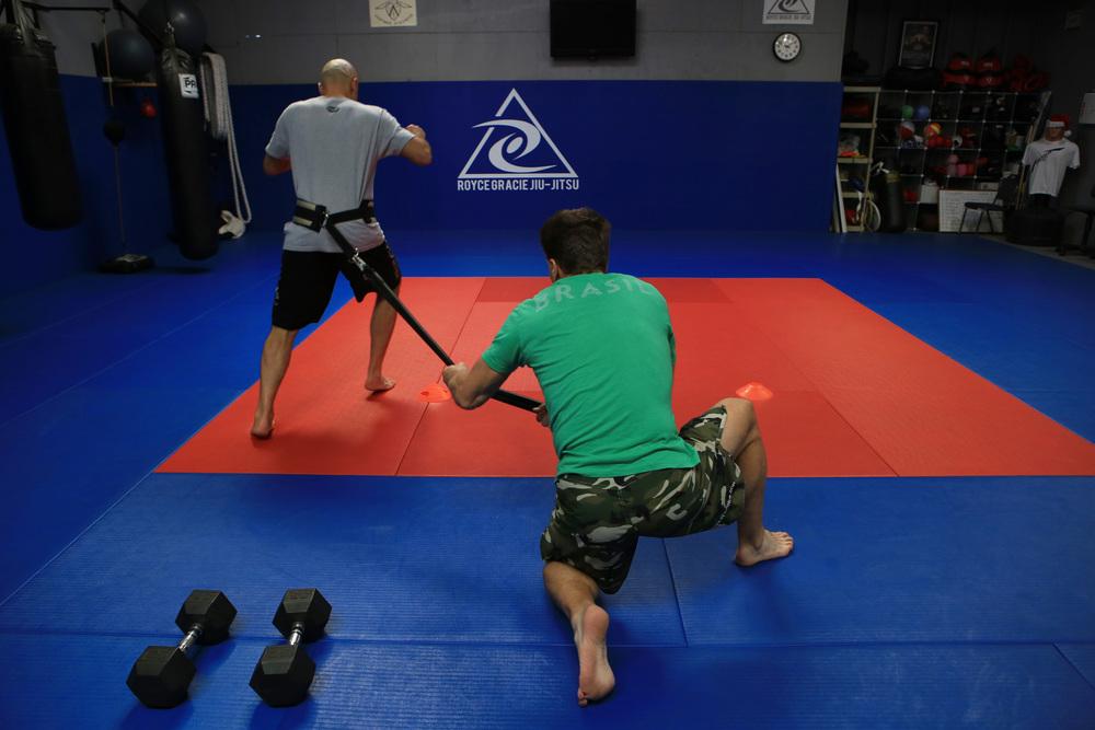 Gracie, left, works on his strength and conditioning with sports trainer, Strom, center, at the Royce Gracie Jiu-Jitsu Academy that he founded to promote mixed martial arts. (©Gail Fisher for ESPN)