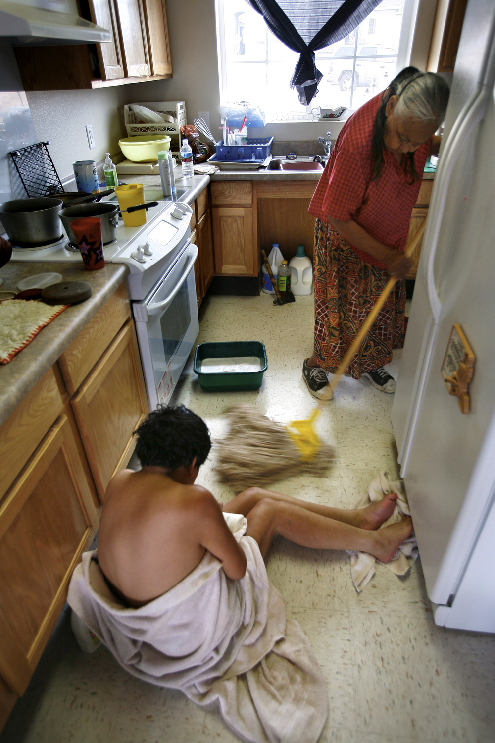 No longer able to get into a bathtub or shower, Laura Neztsosie is bathed by her mother out of bucket on the kitchen floor. ©Gail Fisher Los Angeles Times