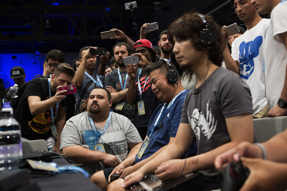 Daigo Umehara is watched intently by fans by cell phones recording the action, during Evolution Championship 2016 Series at the Mandalay Bay Events Arena in Las Vegas, Nevada.  © Gail Fisher for ESPN