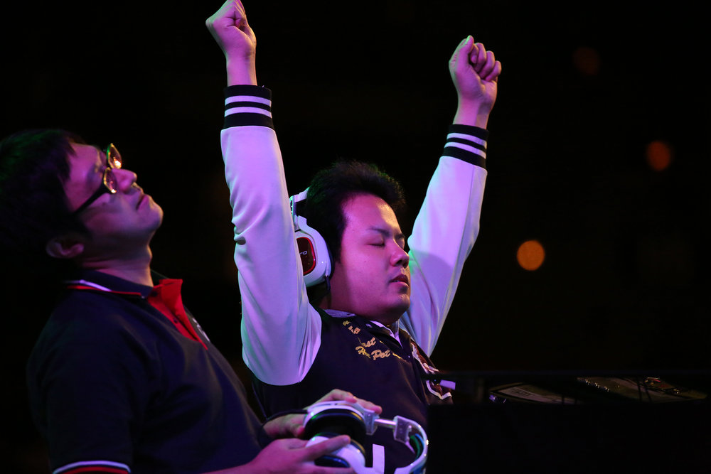 "Omito ""Omito"" Hashimoto throws his hands up after a 3-1 victory over Rion in the Guilty Gear loser's finals. © Gail Fisher for ESPN"
