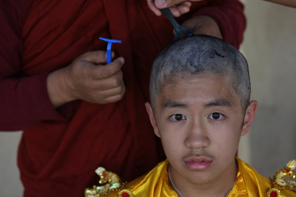 Ashin Gunissara shaves the head of Filbert Win Min Aung. The shaving of the head symbolizes giving up vanity. © Gail Fisher for Los Angeles Times