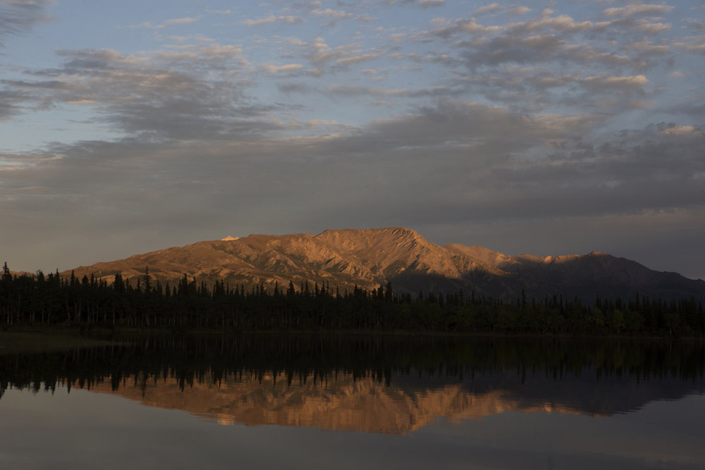Sun sets over tranquil Otto Lake with views of Mt. Healy and Mt. Dora as a backdrop in Healy, Alaska, ten miles north of north of Denali National Park and Preserve. © Photo by Gail Fisher
