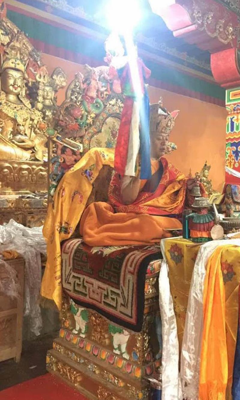 Tulku Orgyen Zangpo Rinpoche at Zabbulung Sindul Palchen, July 2015, with Guru Rinpoche statue in the background.