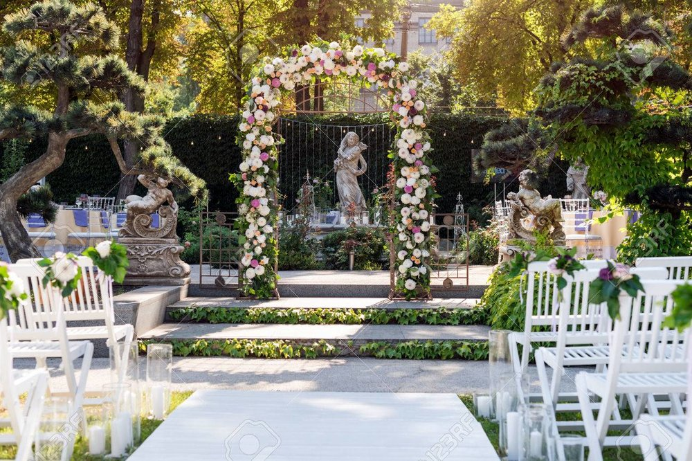 84149403-wedding-arch-with-flowers-outdoors-beautiful-wedding-set-up-wedding-ceremony-in-the-garden-with-scul.jpg