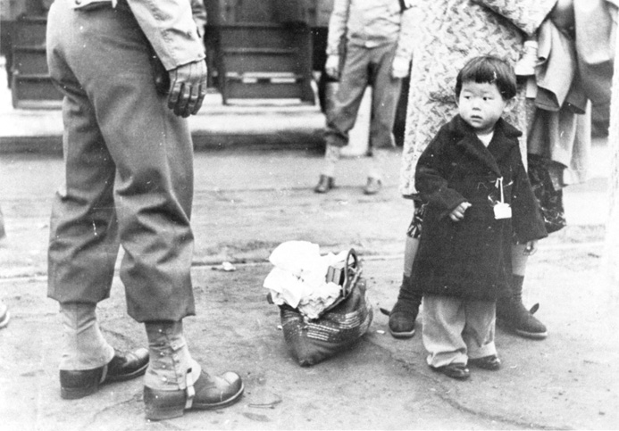 A JAPANESE AMERICAN CHILD is tagged for incarcEration in Los Angeles, California. FrOM THE VISUAL COMMUNICATIONS ARCHIVES.