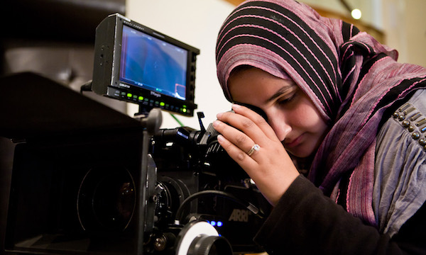 "DIRECTOR LENA KHAN LINES UP A SHOT ON THE SET OF HER FEATURE NARRATIVE DEBUT, ""THE TIGER HUNTER,"" THE FILM FESTIVAL'S OPENING NIGHT PRESENTATION. (PHOTO: COURTESY THE FILMMAKER)"