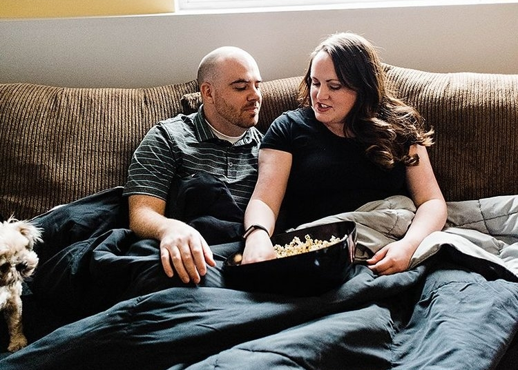 Couple eating popcorn and talking on couch