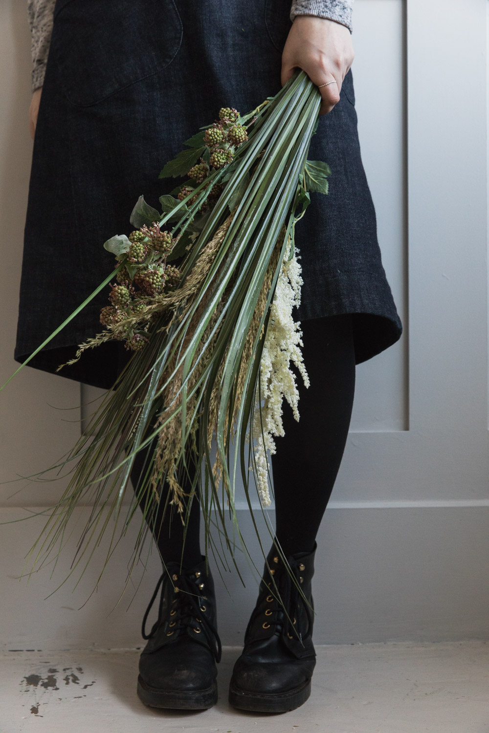 Holding bouquet of grasses by apron