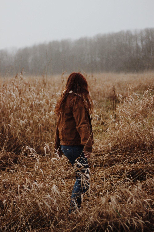Girl in field, misty landscape