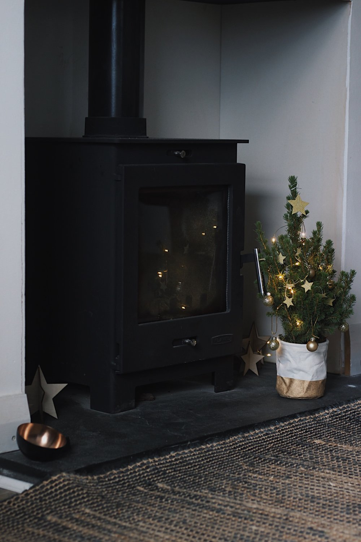 Christmas tree next to wood burning stove