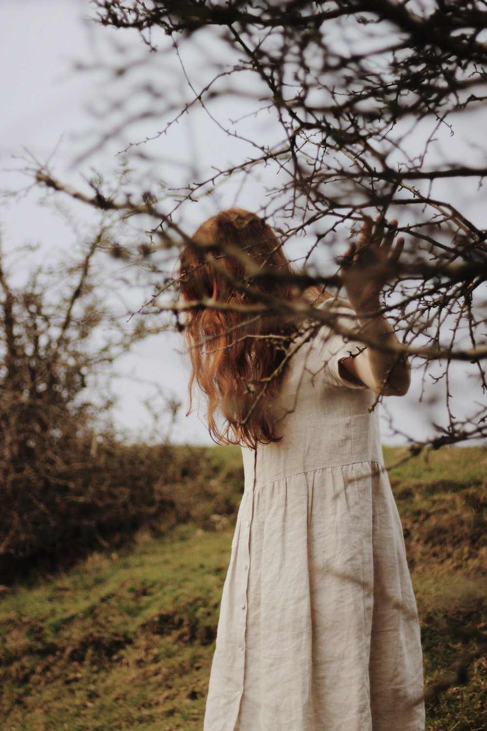 Girl in the countryside wearing a linen dress with red hair