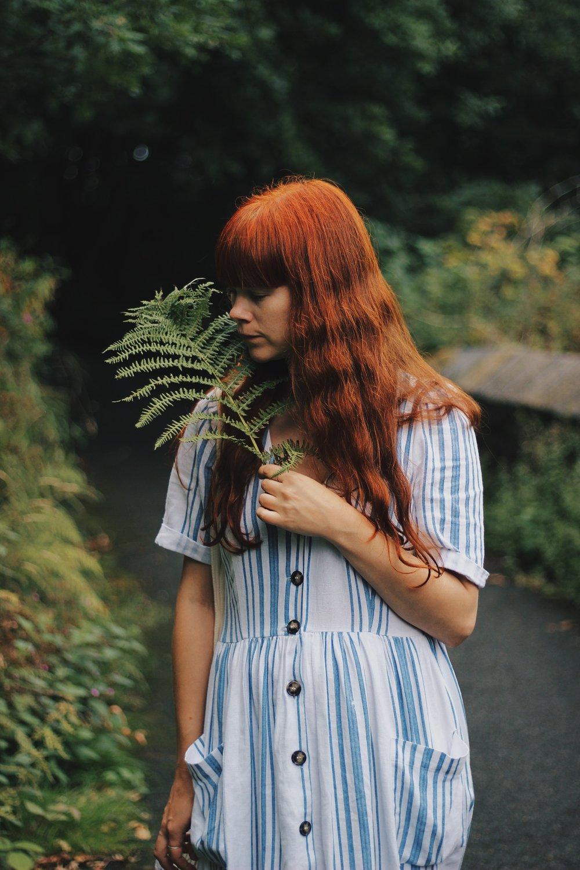 Red haired girl wearing linen summer dress
