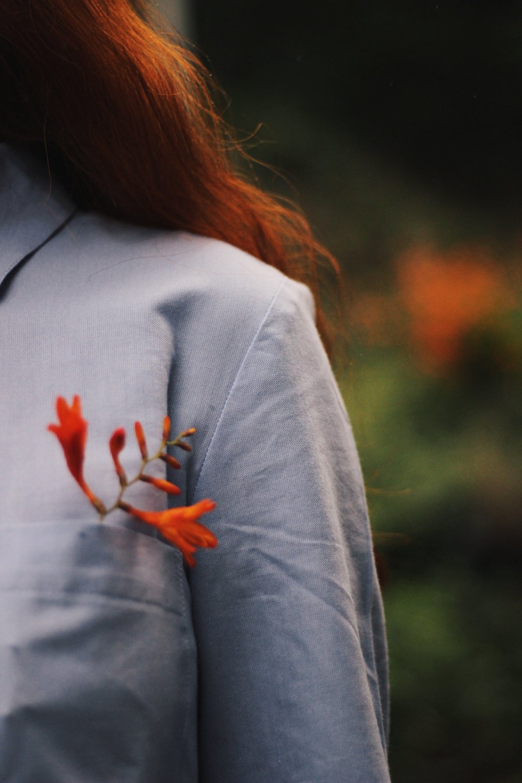 Girl wearing shirt dress, flowers in pocket