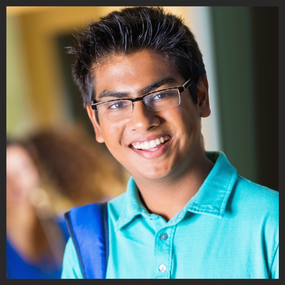 boy with glasses smiling and happy