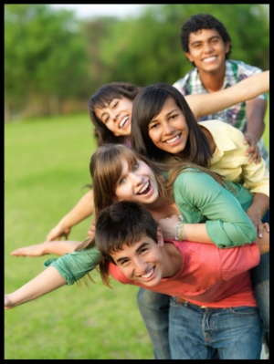 group of teenagers stacked on top of each other smiling