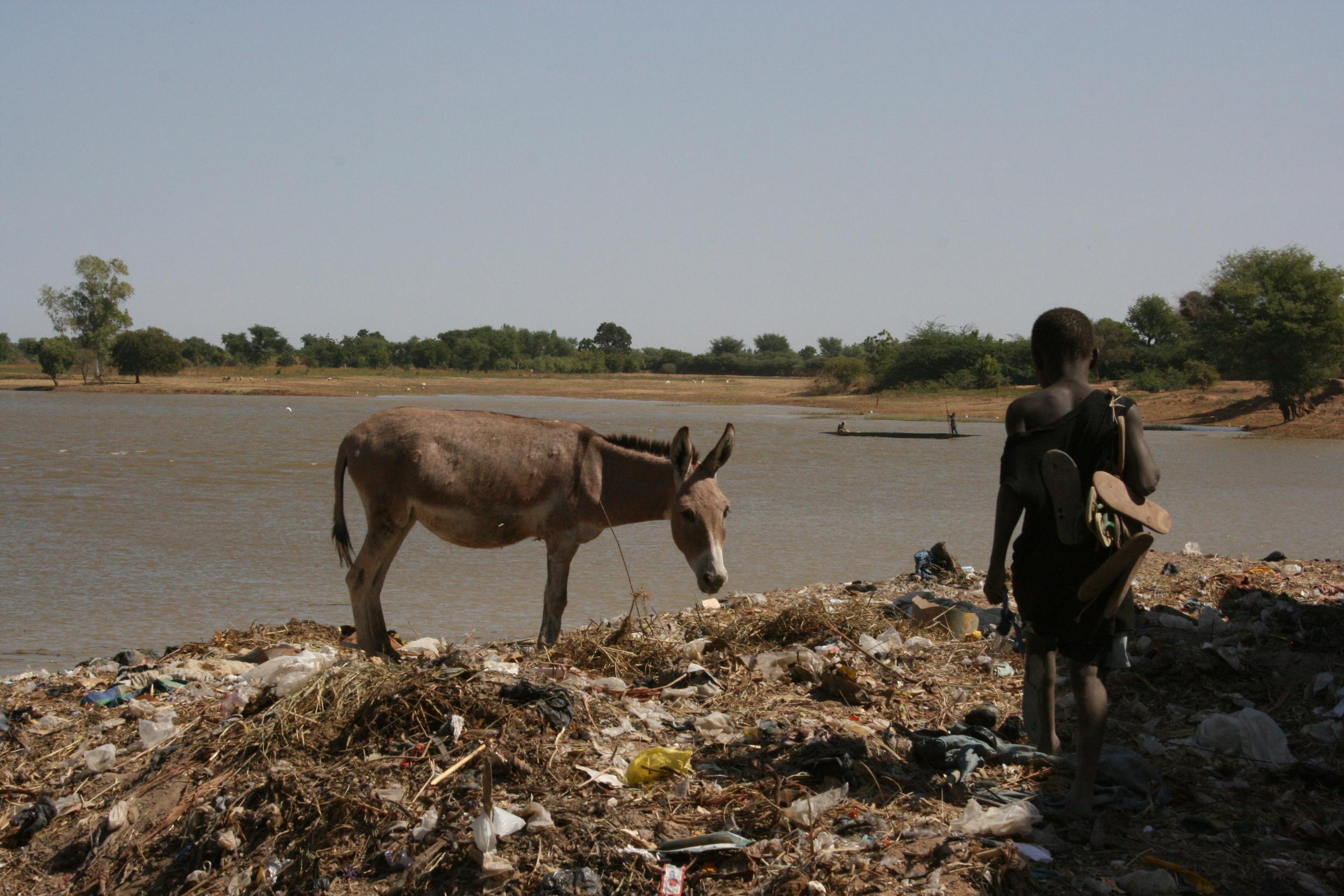 Child on rubbish tip beside river in Djenne, Mali