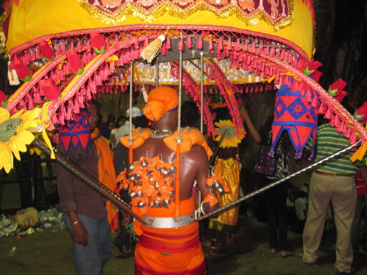 An intricate kavadi that merges both the canopy and individual milk pots as offerings for Lord Skanda/ Muruguan.