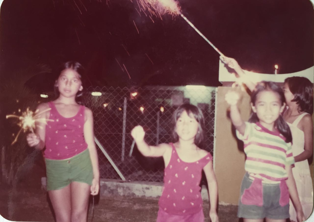 My sister Fez (left) and I (centre) in identical t-shirts (left) with cousins at my grandparent's house in Ipoh circa 1979 - yup my sparkler had run out but I still looked happy!