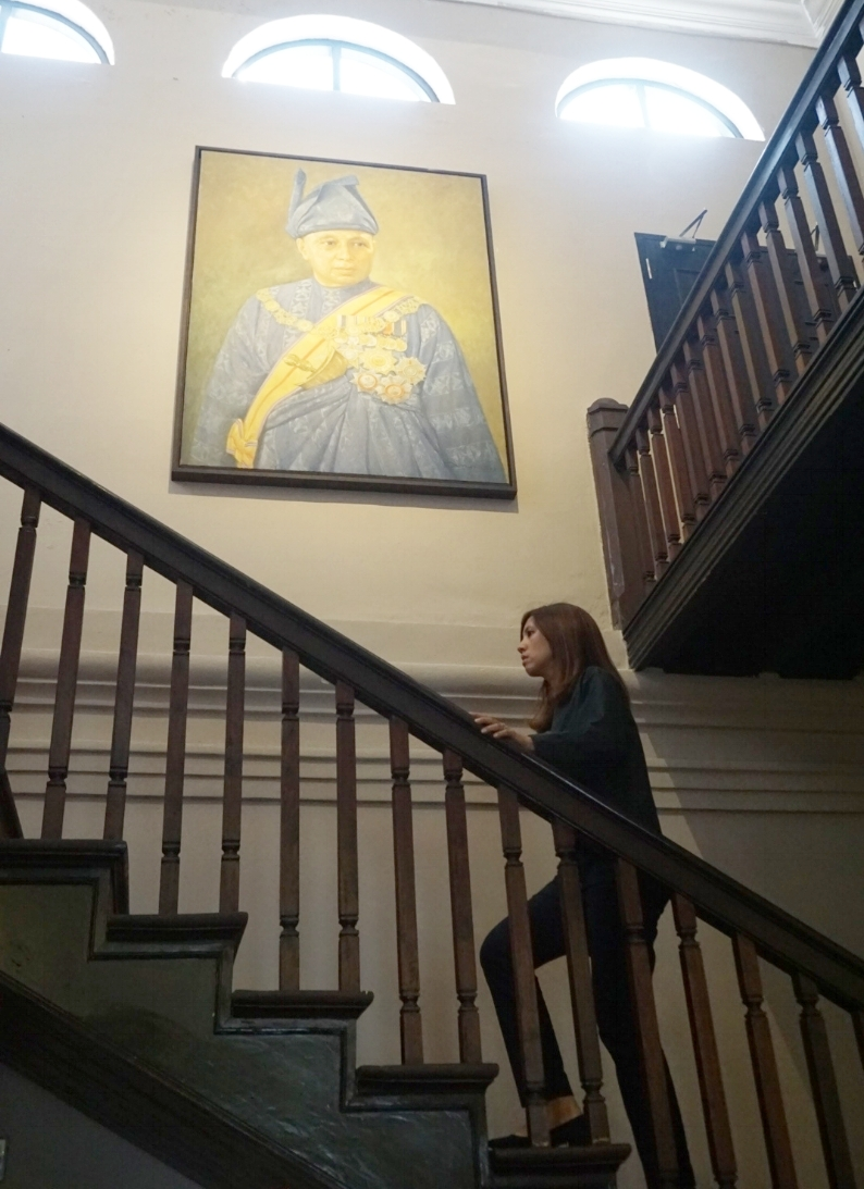 Walking up the original wooden staircase that leads up to the 1st floor of Muzium Sultan Abu Bakar ~ - an original portrait of Sultan Abu Bakar gives a commanding presence to the room
