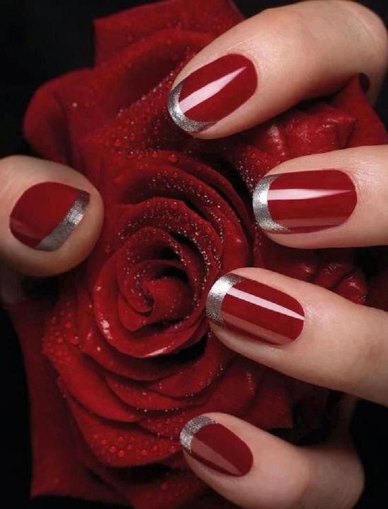 hand with red nails and silver tips holding red rose