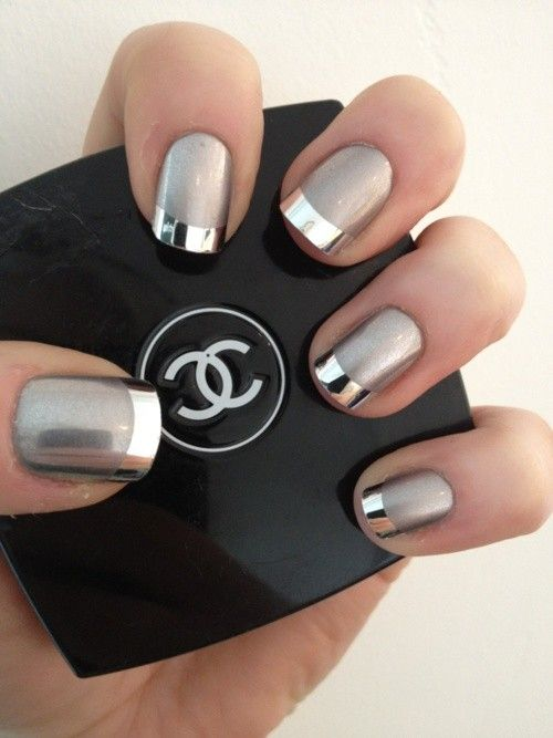 hand with silver and grey nails holding chanel makeup