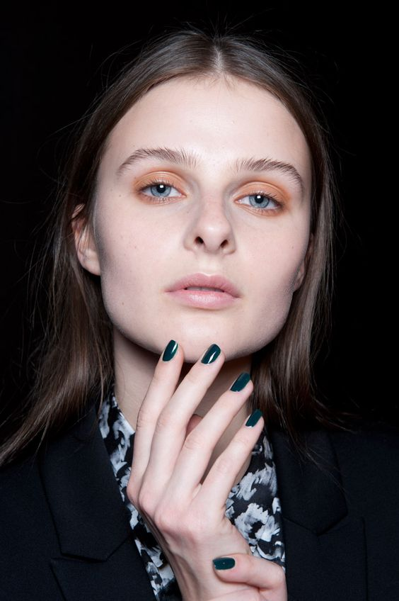 brunette female model with blue eyes, orange eye shadow and teal nails holding her chin wearing black blazer and floral shirt
