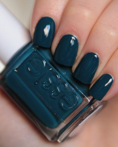 hand with teal nails holding teal essie nail polish