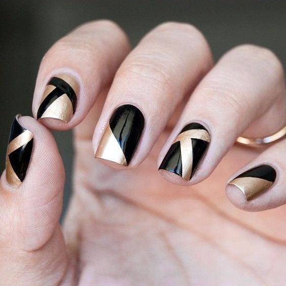 hand with geometrical black and gold nail art