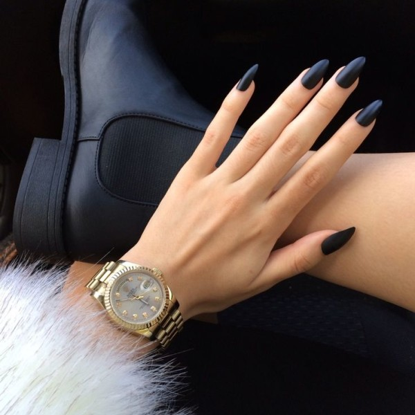 hand with long navy nails and furry sleeve