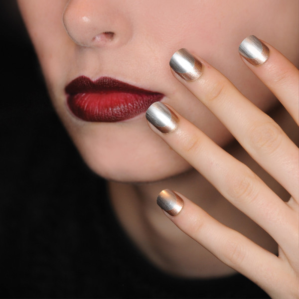 hand with silver nails held up against womans face with red lipstick