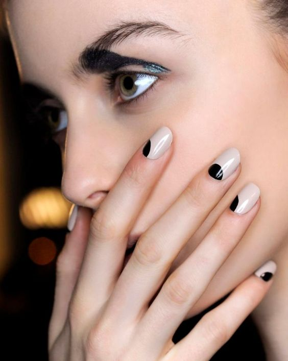 female model holding her mouth with black and white nails