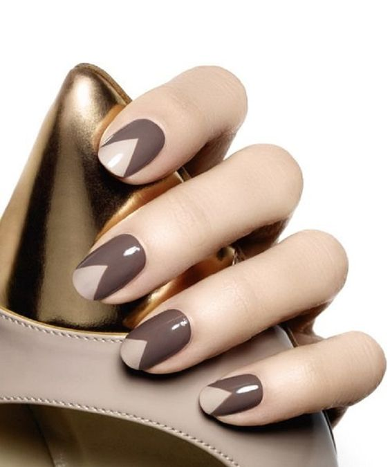 hand with brown and beige nails holding gold bag