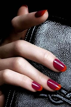 hand with red nails and red tips holding bag