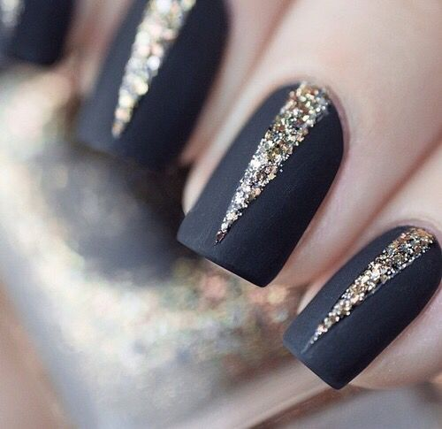 hand with black nails and glitter through the middle