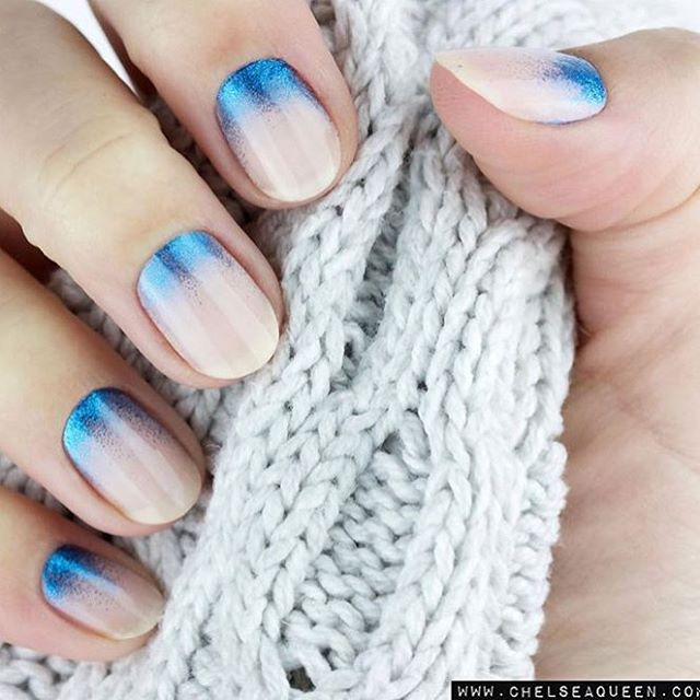 hand with blue and natural nails holding knitwear