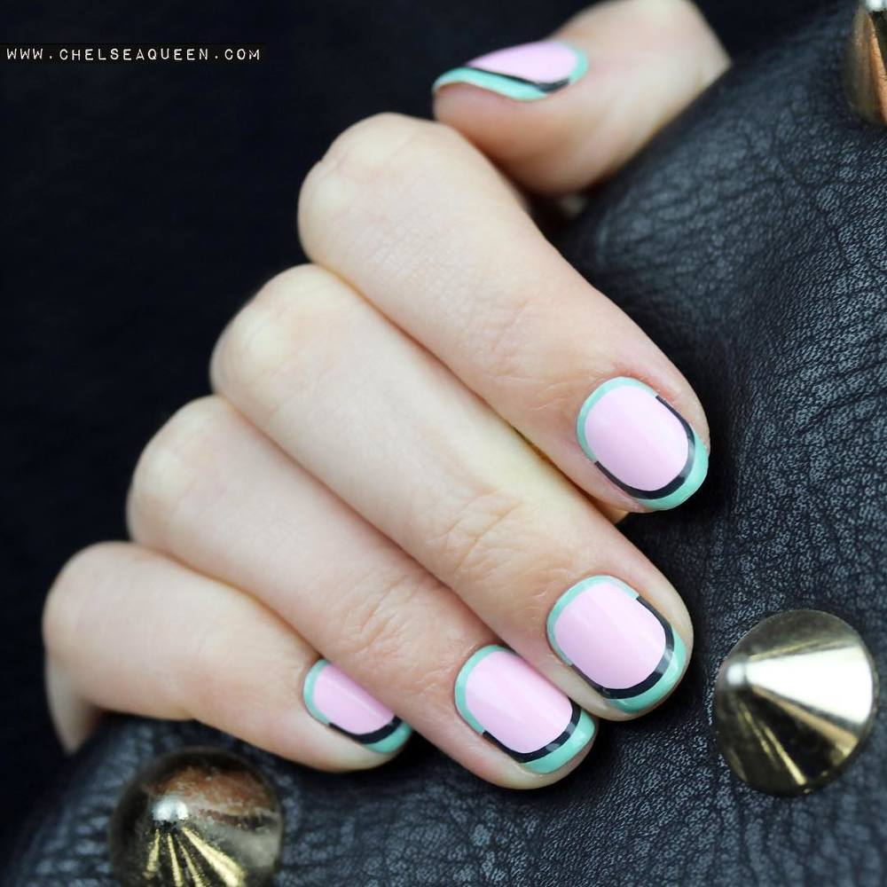 hand with green and pink nails holding black purse with studs