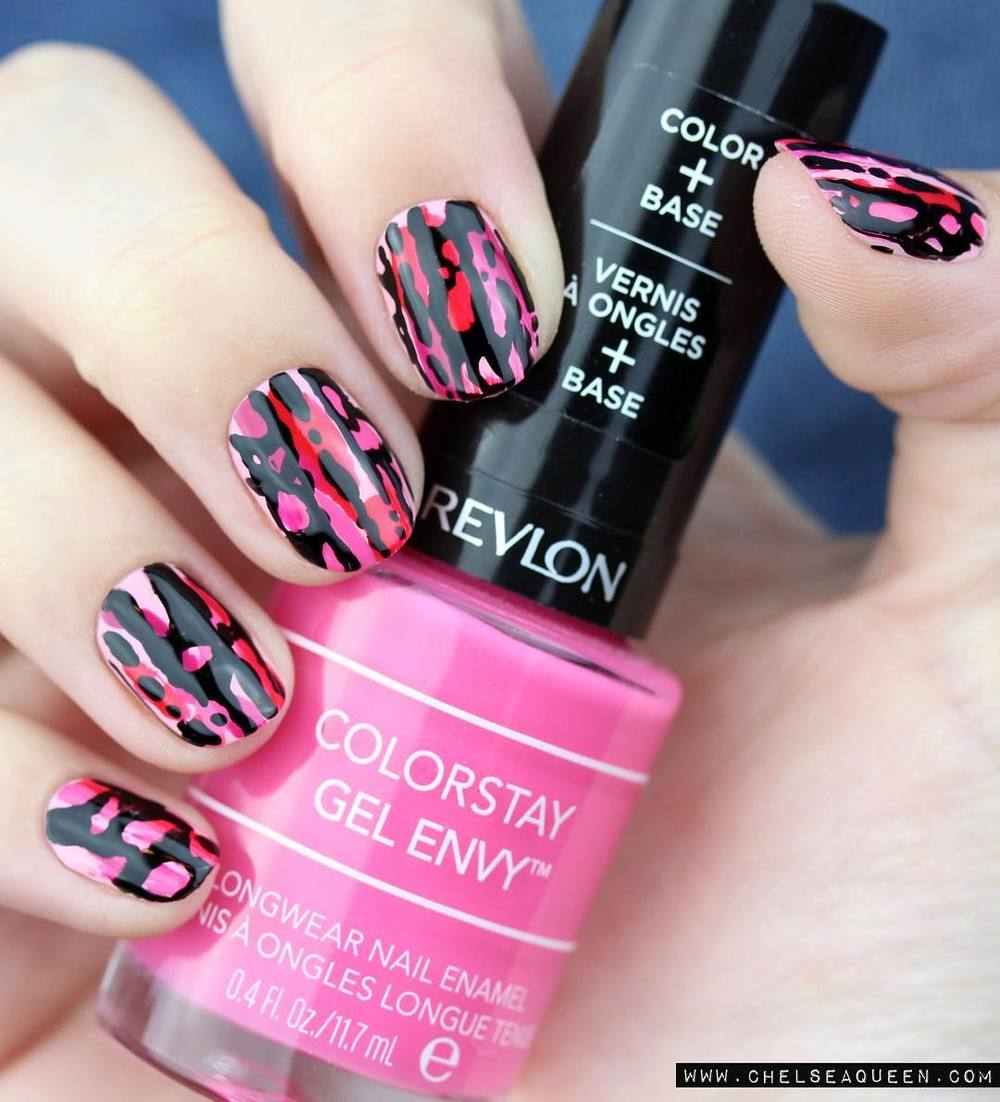hand with black nails and pink patterns holding pink revlon nail polish