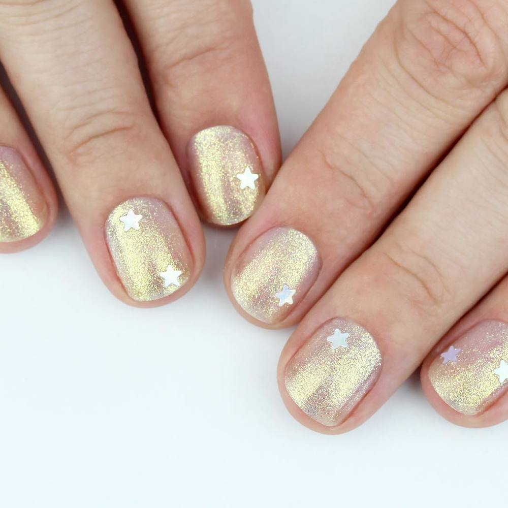 two hands with gold nails laid on a white bench