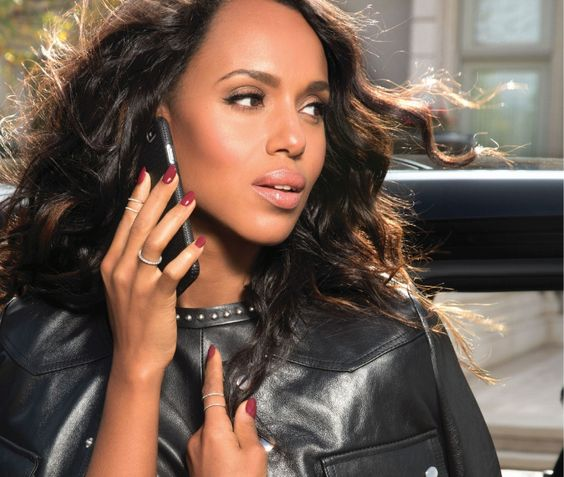 Kerry Washington posing on an iphone wearing a leather jacket with maroon nails