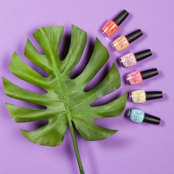 a range of opi nail polishes spread out against a purple background around a green leaf