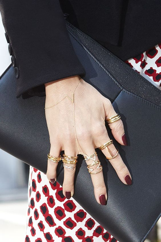 woman's hand dressed in gold jewellery and maroon nails holding a black clutch in and red, white and black dress