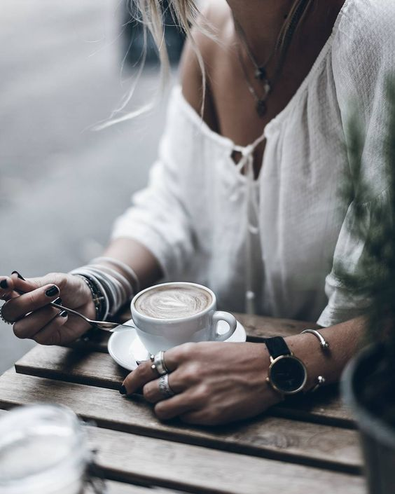 Woman in white off shoulder top and black watch holding spoon next to coffee