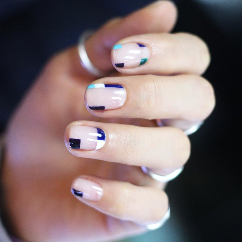 A hand with geometric patterns on nails