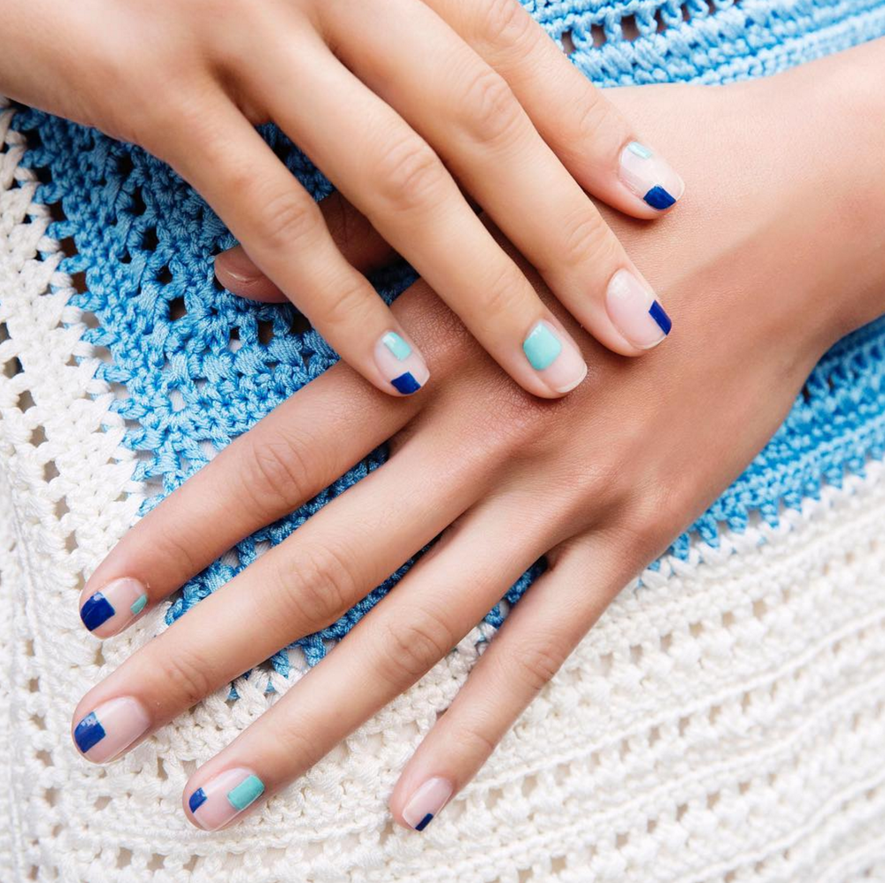 two hands with geometric patterns on nails