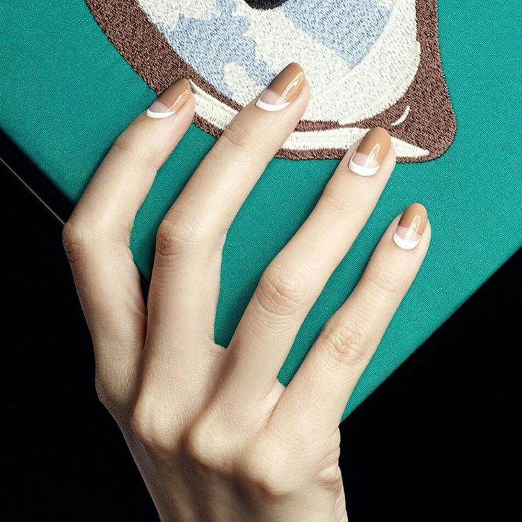 hand holding a green and brown clutch with brown and white nails