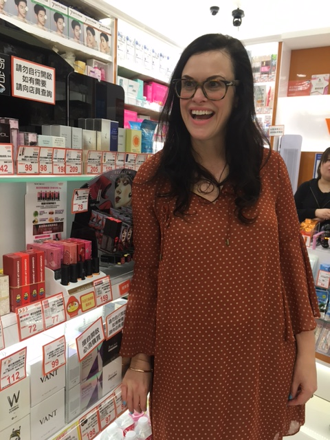 Woman in burnt orange top at beauty store