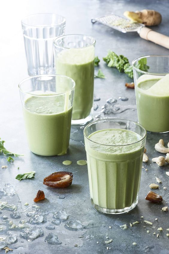 Glass cups with green smoothies inside on a table with different ingredients such as nits and ginger inside
