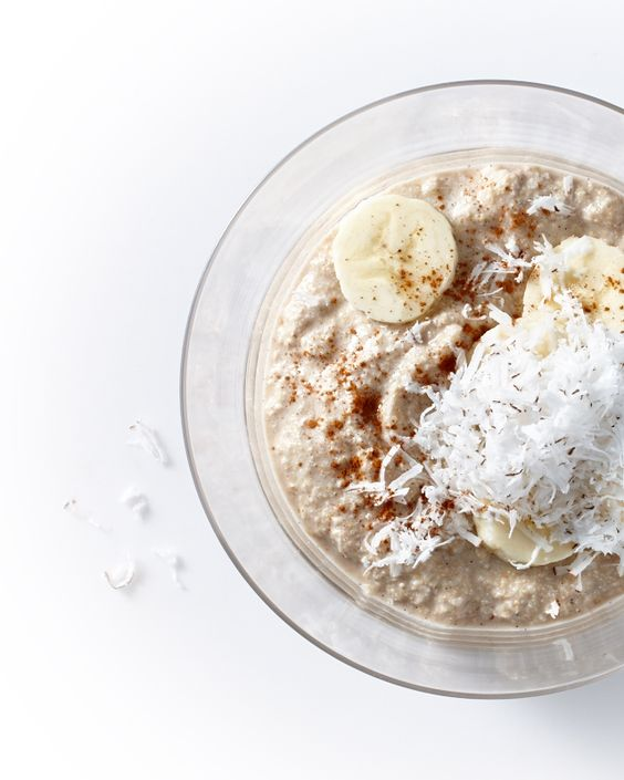 Bowl of oats with banana slices and coconut flakes on top