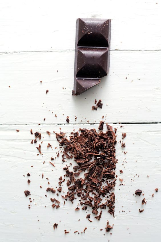 Dark chocolate blocks and shavings on white table