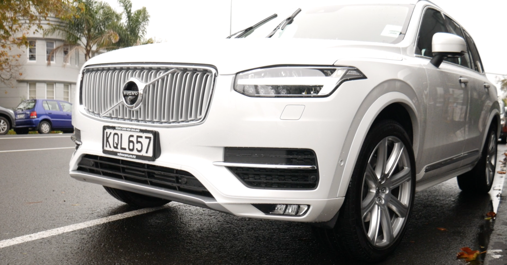 The front of a white Volvo showing the grill and front tyres